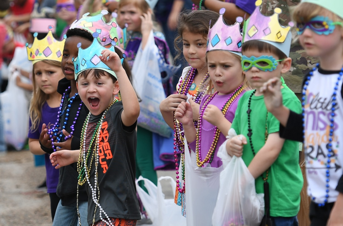 Children line the streets yelling for beads to be thrown his way while standing among class mates during the Jeff Davis Elementary School Mardi Gras parade in Biloxi, Mississippi, March 1, 2019. Keesler leadership, Honor Guard and Airmen participated in various festivities throughout the Mardi Gras season, which is celebrated by the local communities. (U.S. Air Force photo by Kemberly Groue)