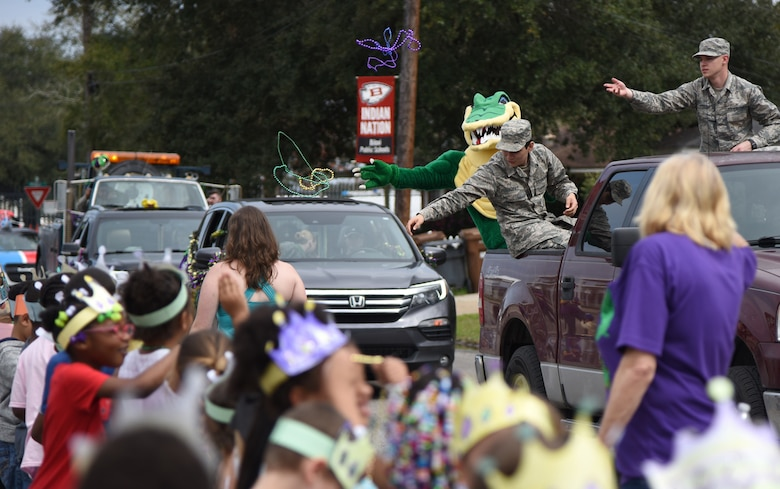 Airmen from the 334th Training Squadron and their mascot, the Gator, toss beads to children during the Jeff Davis Elementary School Mardi Gras parade in Biloxi, Mississippi, March 1, 2019. Keesler leadership, Honor Guard and Airmen participated in various festivities throughout the Mardi Gras season, which is celebrated by the local communities. (U.S. Air Force photo by Kemberly Groue)