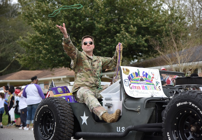 U.S. Air Force Col. Lance Burnett, 81st Training Wing vice commander, tosses beads to children during the Jeff Davis Elementary School Mardi Gras parade in Biloxi, Mississippi, March 1, 2019. Burnett and Chief Master Sgt. Ricardo Russo, Keesler Medical Center superintendent, served as the Grand Marshals while other base personnel also participated in the event. Keesler leadership, Honor Guard and Airmen participated in various festivities throughout the Mardi Gras season, which is celebrated by the local communities. (U.S. Air Force photo by Kemberly Groue)