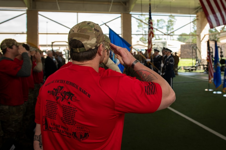 A Special Tactics Airman with the 24th Special Operations Wing salutes during the presentation of colors during the Special Tactics Ruck March Memorial Ceremony at Hurlburt Field, Florida, March 4, 2018.