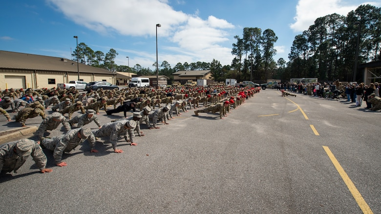 Special Tactics senior leaders with the 24th Special Operations Wing lead hundreds of Air Commandos, teammates and family in performing memorial push-ups following the Special Tactics Ruck March Memorial Ceremony at Hurlburt Field, Florida, March 4, 2018.