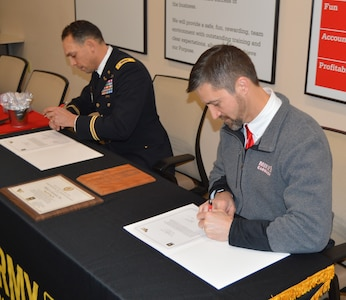 Two men sitting at a table sign documents. The man on the left is wearing dress blue Army uniform and the man on the right is wearing a grey zip up fleece.