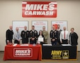 Service members and staff from Mike's Car Wash gathering around a partnership table with the US Army logo on the right side and a Mikes Car Wash logo on the left side. There are ten people total in the photo. Soldiers are in dress blues and multicam. Other men are wearing shirts and ties and the woman are dressed in work attire. In the background there is a big red Mike's Car Washing sign with their values and members promise posters underneath it.