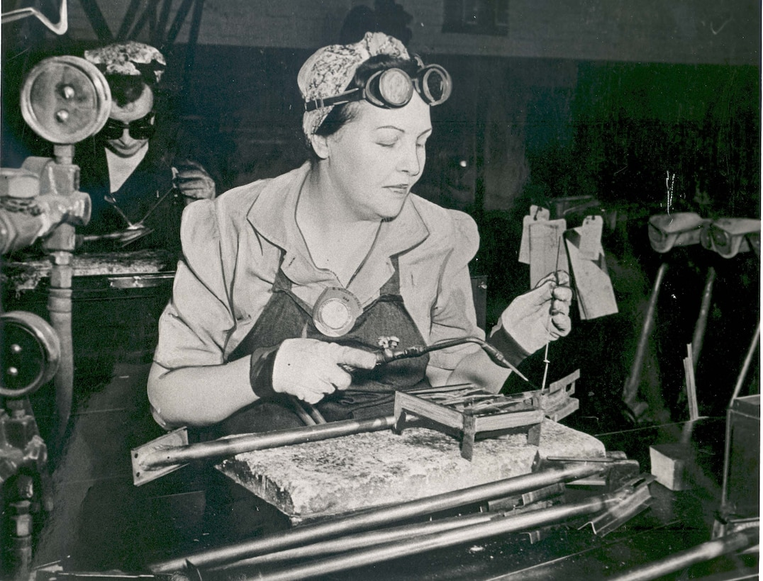 Two women weld sitting at tables.