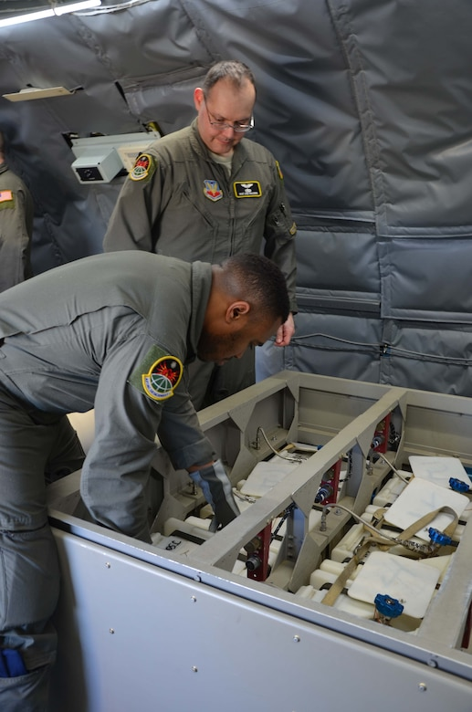 U.S. Air Force Senior Airman Victor Williams (front) repositions a whole air sphere aboard the WC-135 Constant Phoenix as Master Sgt. Jose Gallegos observes.  The Airmen, both special equipment operators, are members of the Air Force Technical Applications Center's Detachment 1 based at Offutt AFB, Neb., and were at Patrick AFB, Fla., to offer tours of the nuclear treaty monitoring aircraft.  (U.S. Air Force photo by Susan A. Romano)
