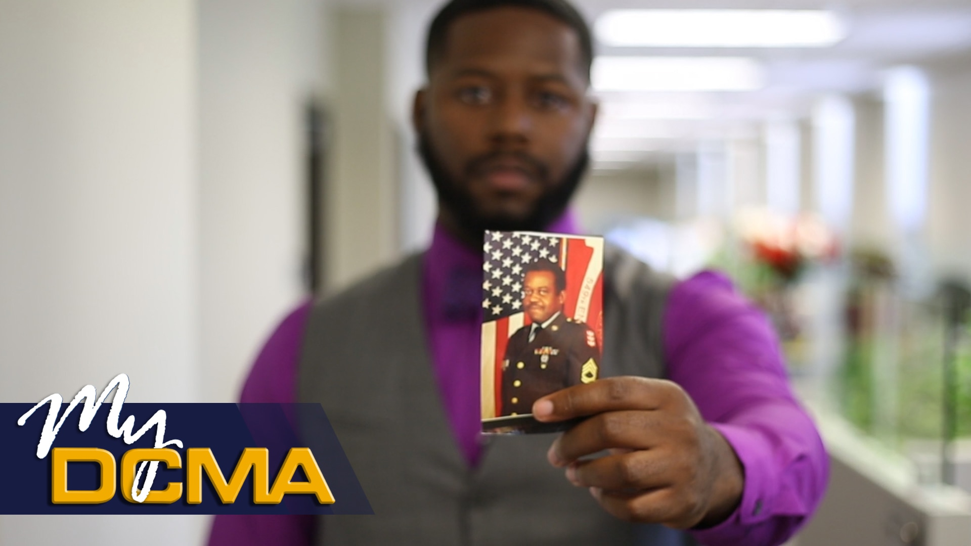 Man holds photo of another man in uniform.