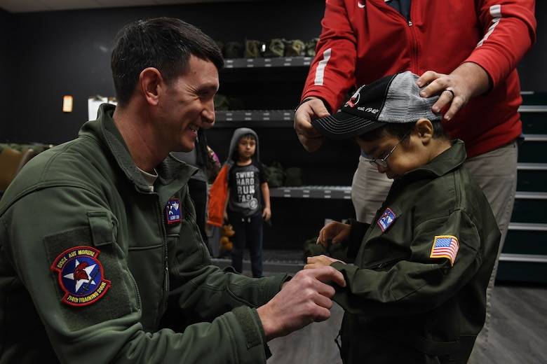 A pilot and helps zip up a jacket for a young boy