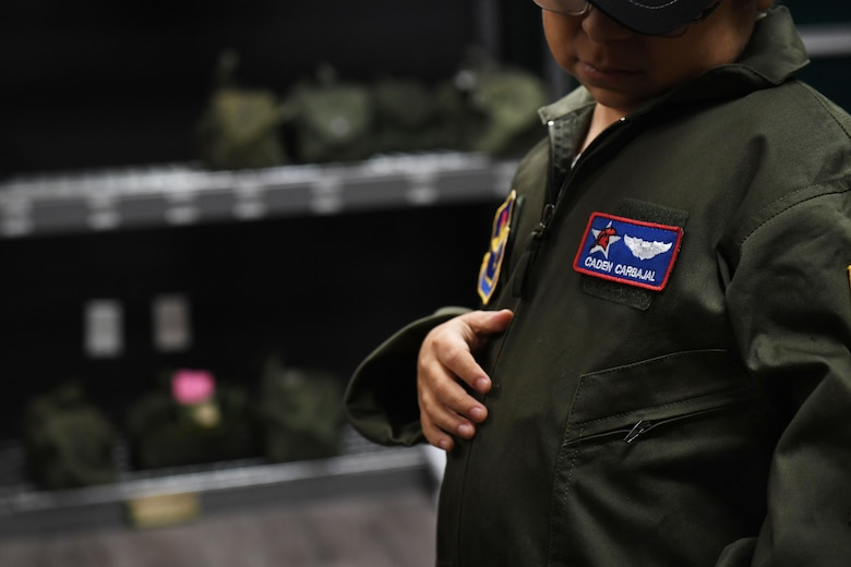 A young boy looks down at his name patch on his new flight suit