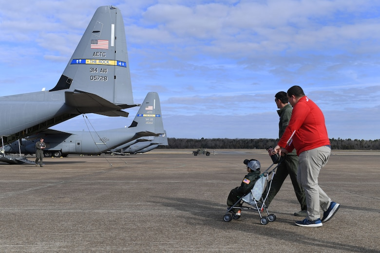 a father pushed his son in a stroller to a C-130J on the flight line