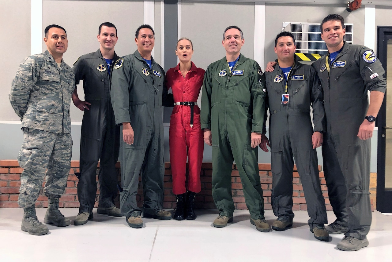 Actress Brie Larson stands in the middle of 6 Air National Guardsmen for a photo.