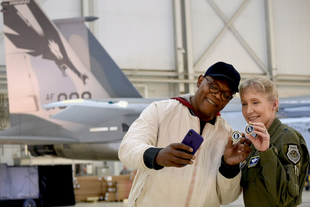 Actor takes photo with airman and challenge coin.