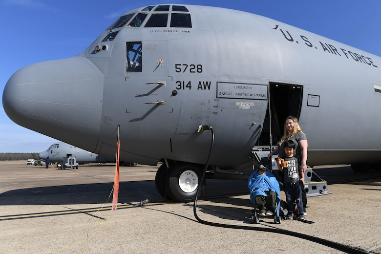A mother and her two sons pose for a photo on the flight line in front of a C-130J airplane.