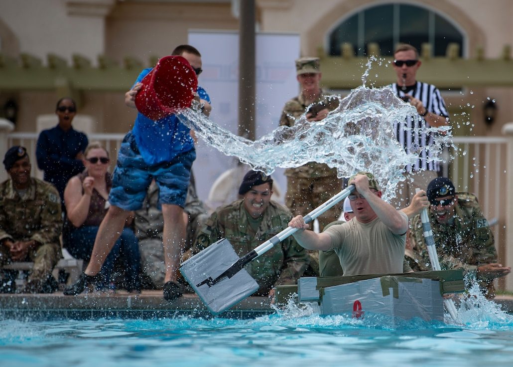 """Staff Sgt. Chad Bohr and Tsgt. Tyler Dalton, 377th Weapons System Security Squadron are splashed by spectators during the Battle of the Battleships, here, Aug. 30. Bohr and Dalton's ship, """"Ops Boat,"""" placed second overall. (U.S. Air Force photo by Staff Sgt. J.D. Strong II)"""