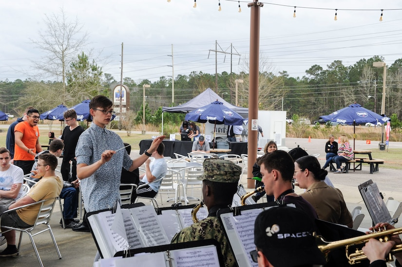 Seaman Briana Buchholtz, Navy Nuclear Power Training Command band conductor, leads the band in a performance during The Dive grand reopening ribbon cutting ceremony March 1, 2019, on the Naval Weapons Station.