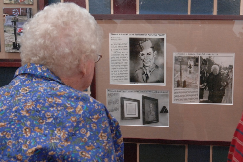 An older woman looks at a group of pictures on a bulletin board.