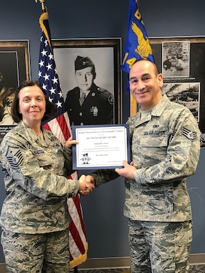 Master Sgt. Angela Hayden, 14th Intelligence Squadron first squadron, presents the December 2018 Diamond Sharp award on behalf of the Wright-Patterson Air Force Base Reserve First Sergeant Council to Staff Sgt. Dennis Quiles Torres, 14 IS CSS Administration Journeyman, for outstanding appearance and superb performance of duties for the month of December 2018.