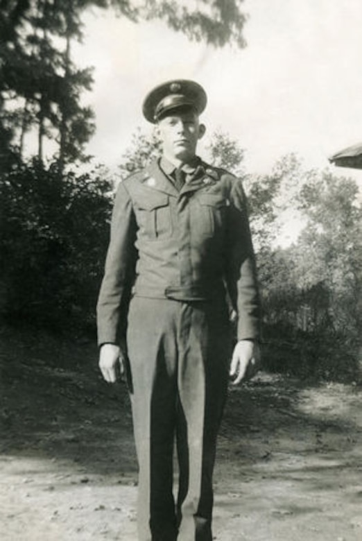 A soldier stands in a field in uniform.