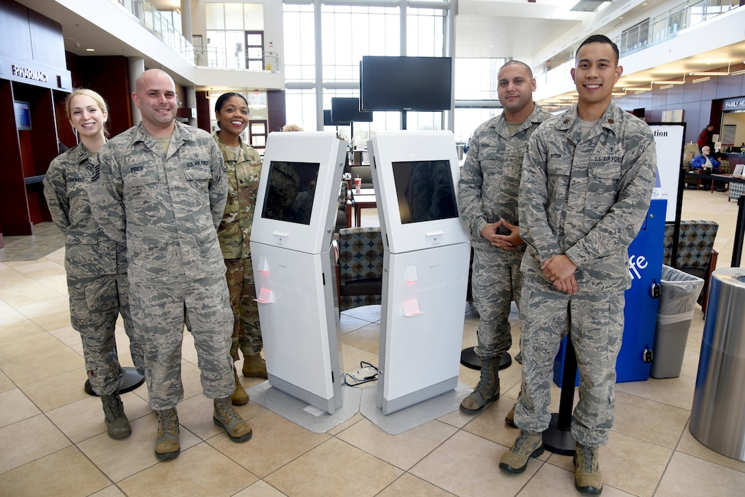 72nd Medical Support Squadron members, from left, First Lt. Jordan Pickell, Master Sgt. Gareth Price, Lt. Col. Theodosia Hill, commander; Tech. Sgt. Karvin Vega and Maj. Karl Bituin, diagnostics and therapeutics flight commander, were the main team members to bring the Q-Flow kiosks to fruition for pharmacy customers. Q-Flow allows customers to check-in to get their prescriptions and then sit in the lobby of the 72nd Medical Group to wait for their pick-up. Q-Flow will show wait times for each customer on the large screens, creating a virtual line, as opposed to standing in an actual line, to receive their prescriptions. (U.S. Air Force photo/Kelly White)