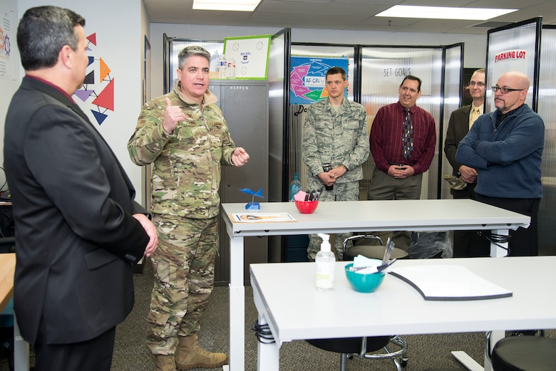 """Col. Jason Lamb (2nd from left), Air Education and Training Command Director of Intelligence, Analysis, and Innovation, speaks to attendees at the grand opening of the command's """"Fire Pit"""" workshop March 5, 2019, at Joint Base San Antonio-Randolph, Texas.  Mirrored to the wing level Spark Cell variant, the AETC Fire Pit is the major command's effort to invigorate innovation and support grassroots initiatives in a collaborative space designed to incubate and accelerate innovation initiatives and build a network with industry, academia, and the Department of Defense to provide rapid solutions to the needs of the warfighter.  (U.S. Air Force photo by Sean Worrell)"""