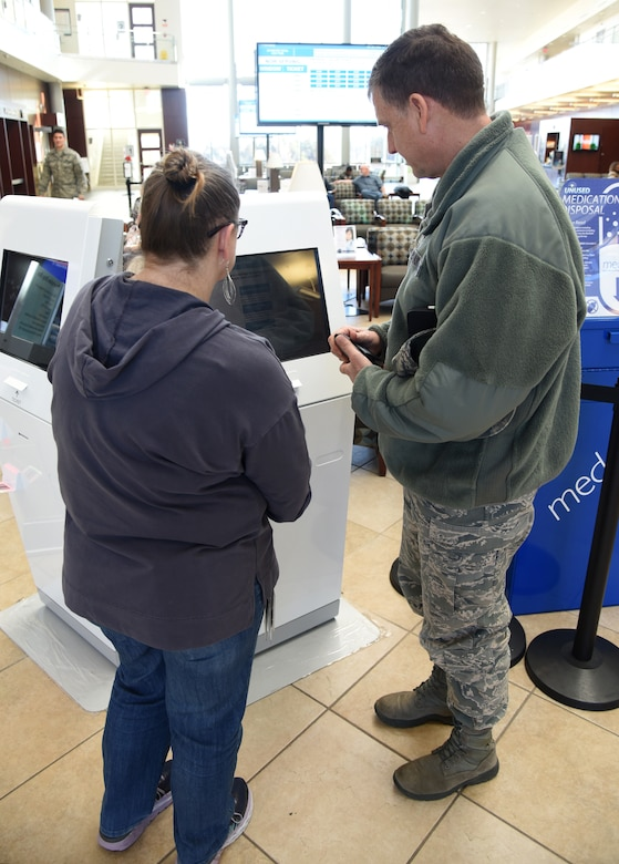 Teresa Larios, pharmacy technician with the 72nd Medical Support Squadron, assists Col. Cliff Altizer, Air Force Sustainment Center Inspector General's Office, with the new Q-Flow machines inside the lobby of the 72nd Medical Group. The Q-Flow kiosks allow pharmacy customers to check-in to pick up their prescriptions and will show them on the large screens in the waiting area what their wait time is. (U.S. Air Force photo/Kelly White)