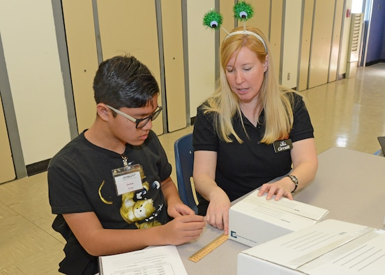 Janet Creech, STARBASE Instructional Systems specialist, shows a student how to calculate the volume of different boxes during the first day of STARBASE classes March 5, 2019. Edwards is one of nine active duty bases with an official STARBASE program. The STEM-based program familiarizes elementary students, primary fifth and sixth graders, from all backgrounds to the world of science, technology, engineering and mathematics. (U.S. Air Force photo by Kenji Thuloweit)