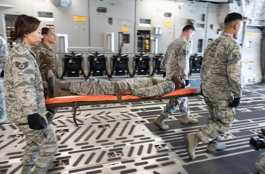 U.S. Air Force Master Sgt. Kassy Costales, back left, and Staff Sgt. Alexandria Davis carry the back end of the patient litter during a training scenario, both are members of the Air Force Reserve's 624th Aeromedical Staging Squadron, at Joint Base Pearl Harbor-Hickam, Hawaii, March 3, 2019.