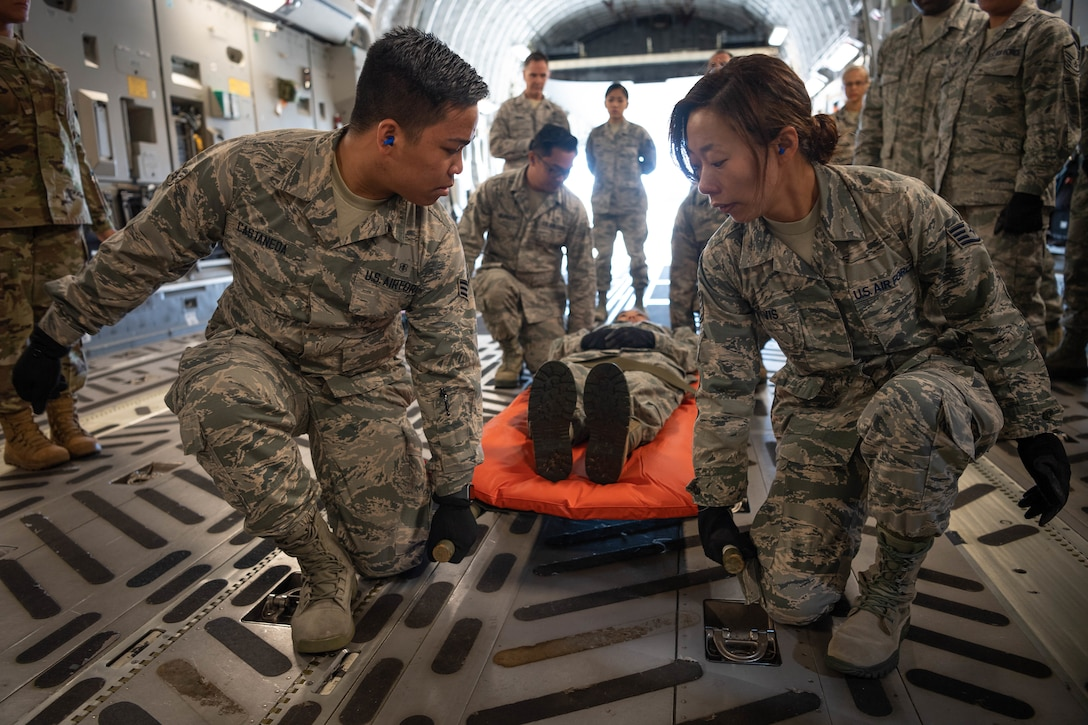 U.S. Air Force Senior Airman Eunel John Castaneda and Staff Sgt. Alexandria Davis, members of the Air Force Reserve's 624th Aeromedical Staging Squadron, carry a simulated patient, Chief Master Sgt. Danyell Stoutamire, during an aeromedical staging and aerial port training at Joint Base Pearl Harbor-Hickam, Hawaii, March 3, 2019. The event was a collaborative effort to build working relationships between the Hawaii Air National Guard and Air Force Reserve, and focused on both medical and aerial port functions to include en route patient care and staging, and cargo preparation and loading. (U.S. Air Force photo by Master Sgt. Theanne Herrmann)