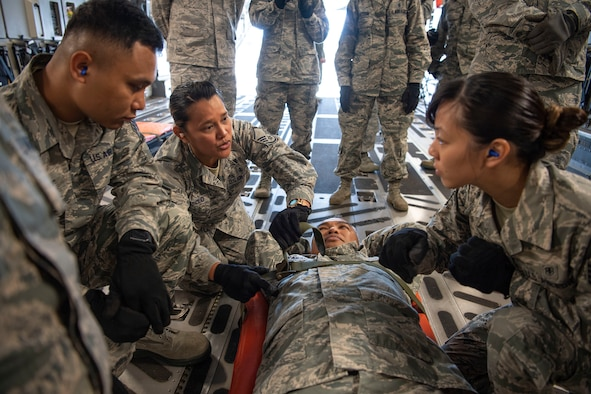 U.S. Air Force Master Sgt. Tatiana Abasolo, a member of the Air Force Reserve's 624th Aeromedical Staging Squadron, provides instruction on how to properly secure a patient for movement during an aeromedical staging and aerial port training at Joint Base Pearl Harbor-Hickam, Hawaii, March 3, 2019.