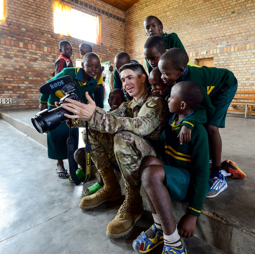 U.S. Air Force Airman 1st Class Noah Coger, 86th Airlift Wing Public Affairs broadcast journalist, shows video to some students of the Home de la vierge des Pauvres Gatagara/Nyanza in the Nyanza District, Rwanda, March 5, 2019. Coger traveled to HVP Nyanza with the U.S. Air Forces in Europe Band, who performed a musical concert for the students. (U.S. Air Forces photo by Tech. Sgt. Timothy Moore)
