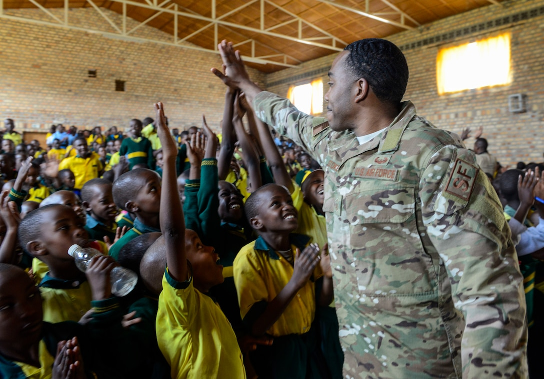 U.S. Air Force Master Sgt. Julius Stokes, Air Force Installation and Mission Support Center Detachment 4, high-fives students of the Home de la vierge des Pauvres Gatagara/Nyanza in the Nyanza District, Rwanda, March 5, 2019. Stokes traveled to HVP Nyanza with the U.S. Air Forces in Europe Band as part of an outreach event. (U.S. Air Force photo by Tech. Sgt. Timothy Moore)