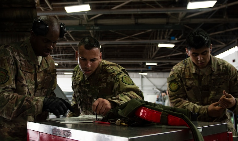 From left, U.S. Air Force Senior Airman Josef Thompson, Staff Sgt. Samuel Ortiz and Airman 1st Class Daniel Nunez, 20th Aircraft Maintenance Squadron, 77th Aircraft Maintenance Unit load crew, review paperwork following load-completion at Shaw Air Force Base, S.C., March 1, 2019.