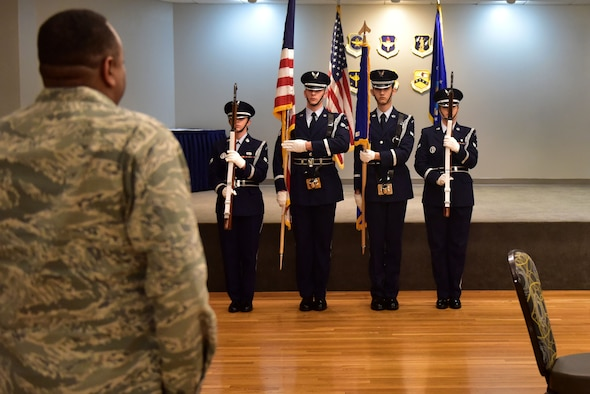 Four Airmen wearing honor guard uniforms present the colors.