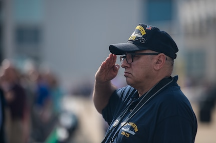 A crewmember from the USS Charleston (LKA-113), an amphibious Navy cargo ship commissioned in 1968, salutes during the new USS Charleston (LCS-18) commissioning ceremony March 2, 2019, in Charleston, S.C.