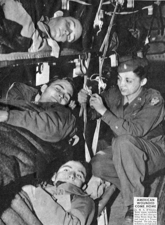 "U.S. Army Air Corps flight nurse 1st Lt. Madeline ""Del"" D'Eletto comforts three wounded soldiers on a flight from the east coast of the U.S. to a Texas hospital. (Courtesy photo by Madeline D'Eletto)"