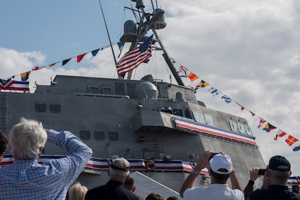 Attendees of the USS Charleston (LCS-18) commissioning ceremony take pictures as its flag is hoisted for the first time March 2, 2019, in Charleston, S.C.