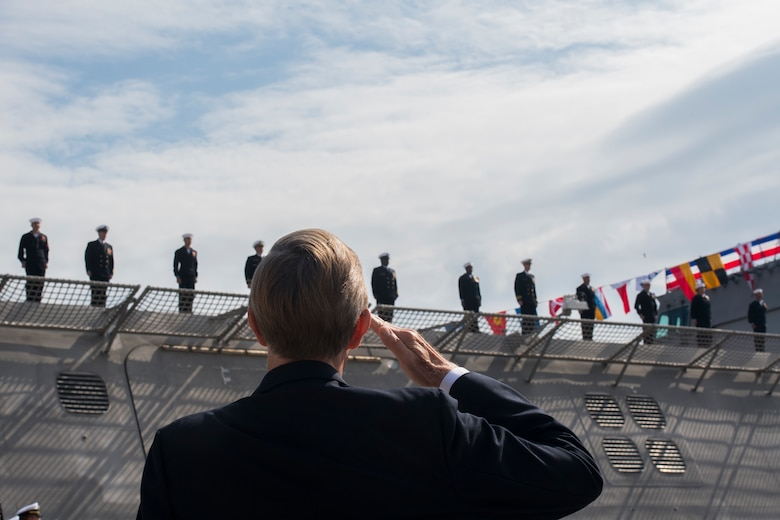 An attendee salutes USS Charleston (LCS-18) crew members as they officially man the ship for the first time at its commissioning ceremony March, 2, 2019, in Charleston, S.C.