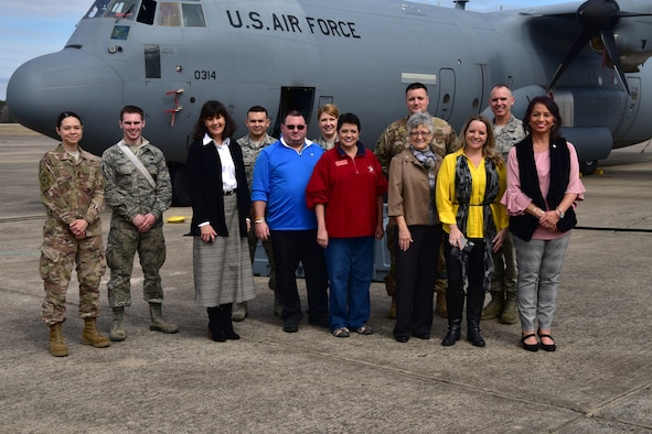 Honorary commanders pose for a photo in fron of a C-130J.