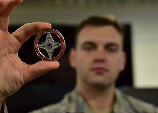 U.S. Air Force Staff Sgt. Brandon Nickell, 8th Intelligence Squadron intelligence analyst, holds a coin presented to him by Chief Master Sgt. James Worrell, 56th Air Communications Squadron superintendent, at Joint Base Pearl Harbor-Hickam, Hawaii, Feb. 25, 2019. Worrell credits Nickell's quick response and care with saving his life. (U.S. Air Force photo by Staff Sgt. Eboni Prince)