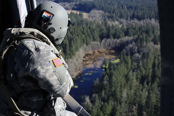 A crew chief on a Black Hawk helicopter watches the placement of a water bucket pendent and relays its information to the pilots during a check ride with the U.S. Forest Service. Washington National Guard aviators conduct water bucket training annually in preparation for wildland fire response.