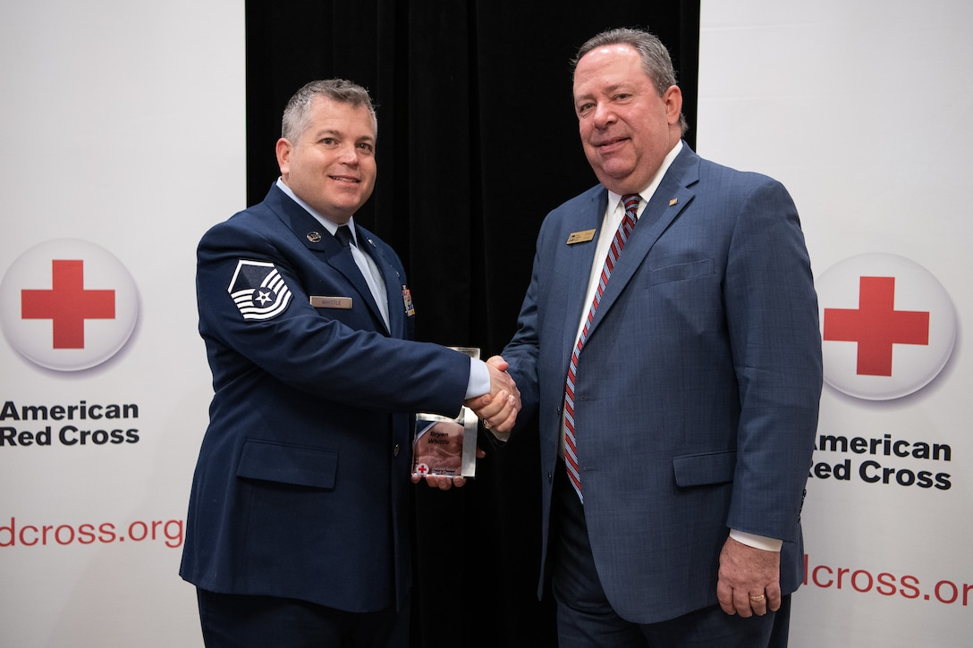 James Finch (right), First Fidelity Bank, shakes hands with Oklahoma Air National Guard Master Sgt. Bryan Whittle, assigned to the 205th Engineering and Installation Squadron at Will Rogers Air National Guard Base, Oklahoma City, after naming him as the American Red Cross of Oklahoma military hero of the year during the 2019 Heroes Breakfast in Oklahoma City, March 5, 2019. Whittle was one of eight people honored for actions in six categories – including military, first responder, healthcare professional, community impact, disaster services and youth – during the first ever Red Cross Heroes Breakfast in Oklahoma City. (U.S. Air National Guard Photo by Tech. Sgt. Kasey M. Phipps)