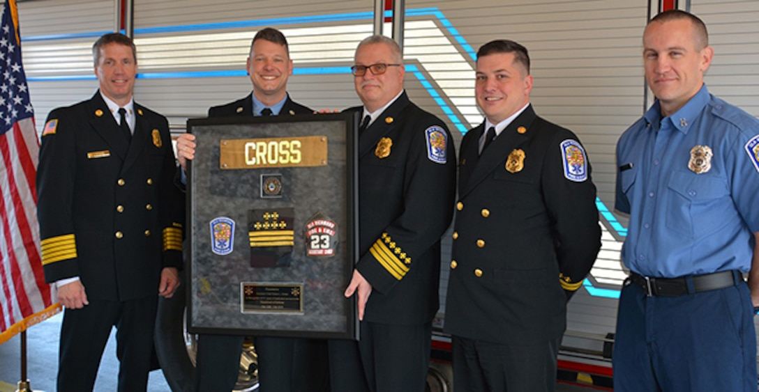 Cross stands with fellow firefighters at his retirement ceremony