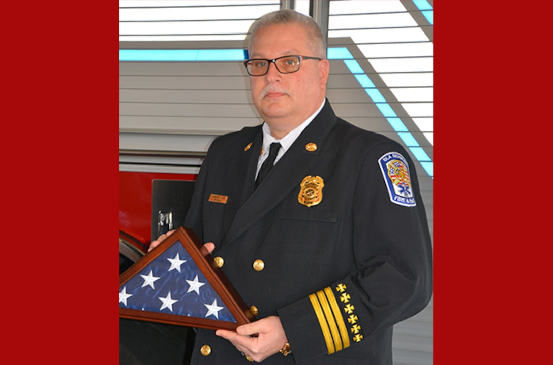 Cross stands with flag at his retirement ceremony