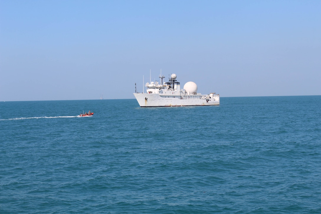 A small rescue boat is seen approaching the USNS Invincible in the Persian Gulf with Invincible mission commander Capt. Paul A. Karsten III aboard.  Karsten, a member of the 22nd Surveillance Squadron at the Air Force Technical Applications Center, Patrick Air Force Base, Florida, was transferred to the ship after the current mission commander was redeployed on emergency leave. (Photo courtesy of the U.S. Coast Guard)