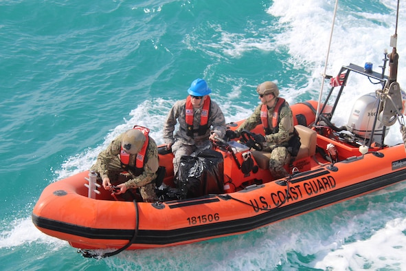 Members of the U.S. Coast Guard transport Capt. Paul A. Karsten III (center) via rescue boat to the USNS Invincible, a radar ship that collects ballistic missile data for the Air Force Technical Applications Center at Patrick Air Force Base, Florida, as part of the center's nuclear treaty monitoring mission. (Photo courtesy of the U.S. Coast Guard)