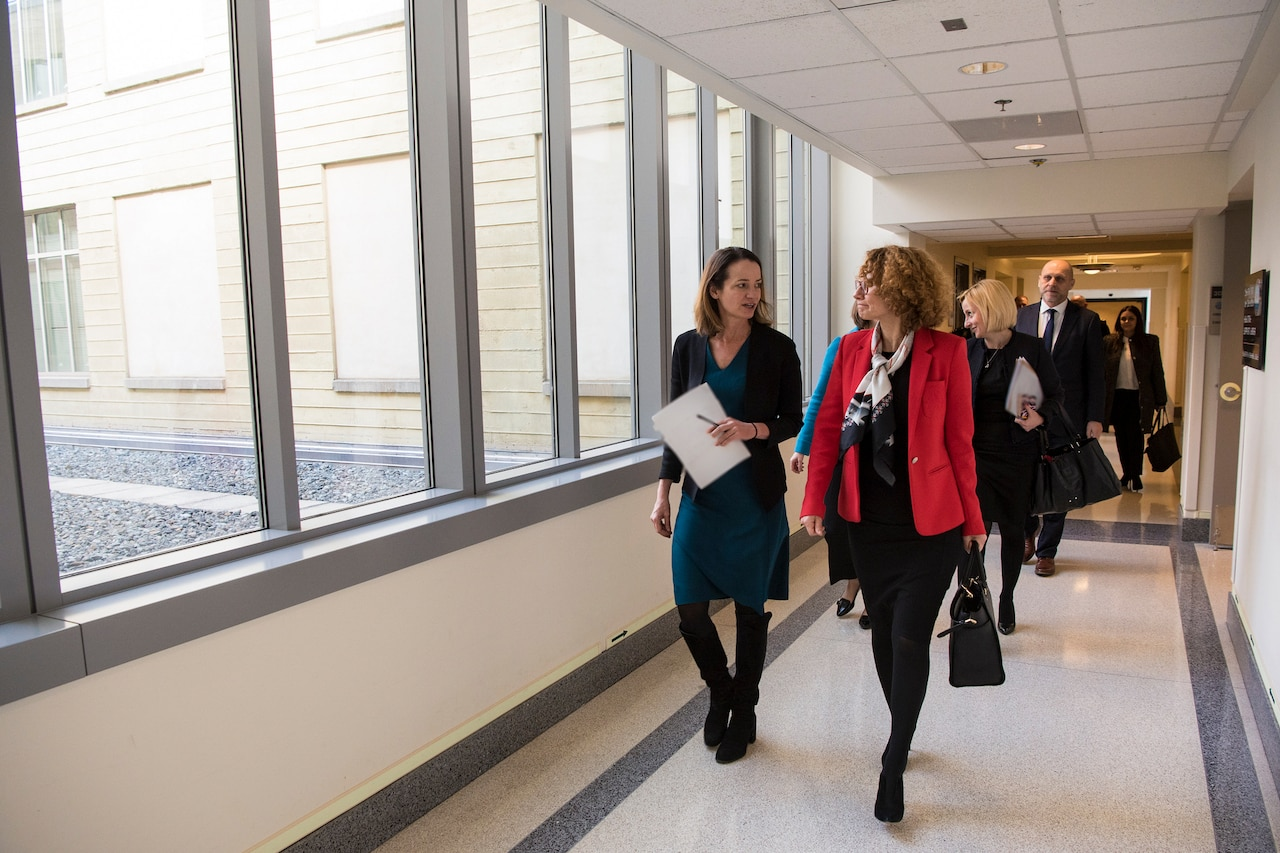 Two women walk down a hallway with a group of people behind them.