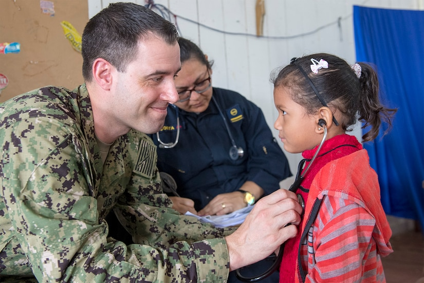 A service member helps a young patient listen to her heartbeat.