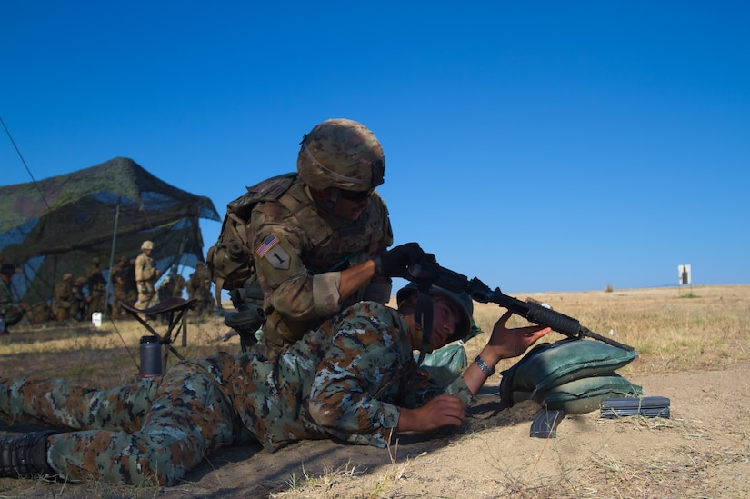 An American soldier checks a Macedonian soldier's rifle during an exercise.