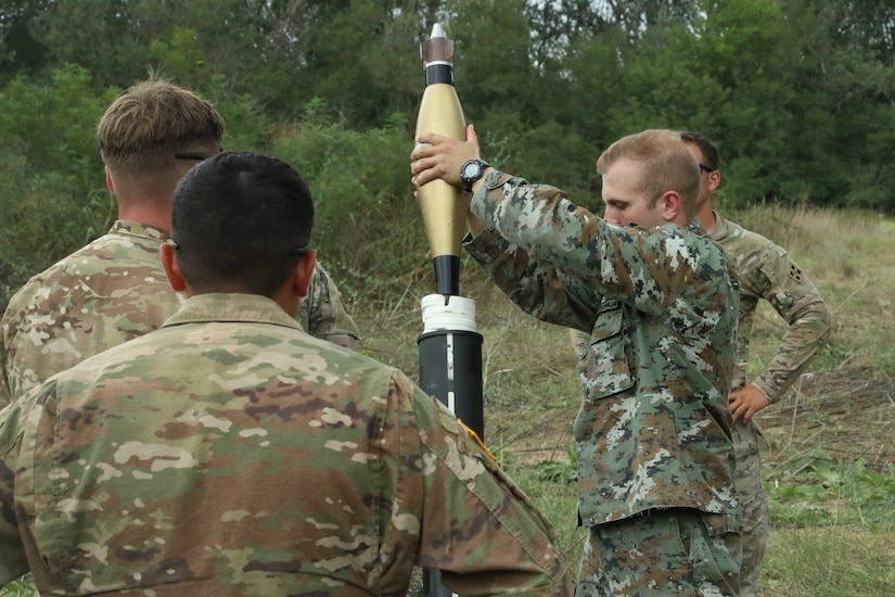 American soldiers observe a North Macedonian soldier placing mortar in mortar tube during an exercise.