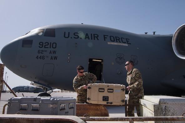 Tech. Sgt. Stephen Shockey, left, 379th Expeditionary Communications Squadron (ECS) Viper team operator, and Master Sgt. Richard Barragan, 379th ECS Viper team lead, move equipment onto a C-17 Globemaster III March 5, 2019, at Al Udeid Air Base, Qatar.
