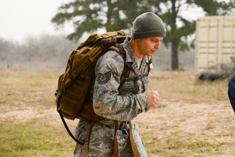 Tech. Sgt. Joshua Porter, 136th Logistics Readiness Squadron vehicle maintainer, pushes toward the finish line after a 12-mile ruck march wearing a 35-pound backpack.